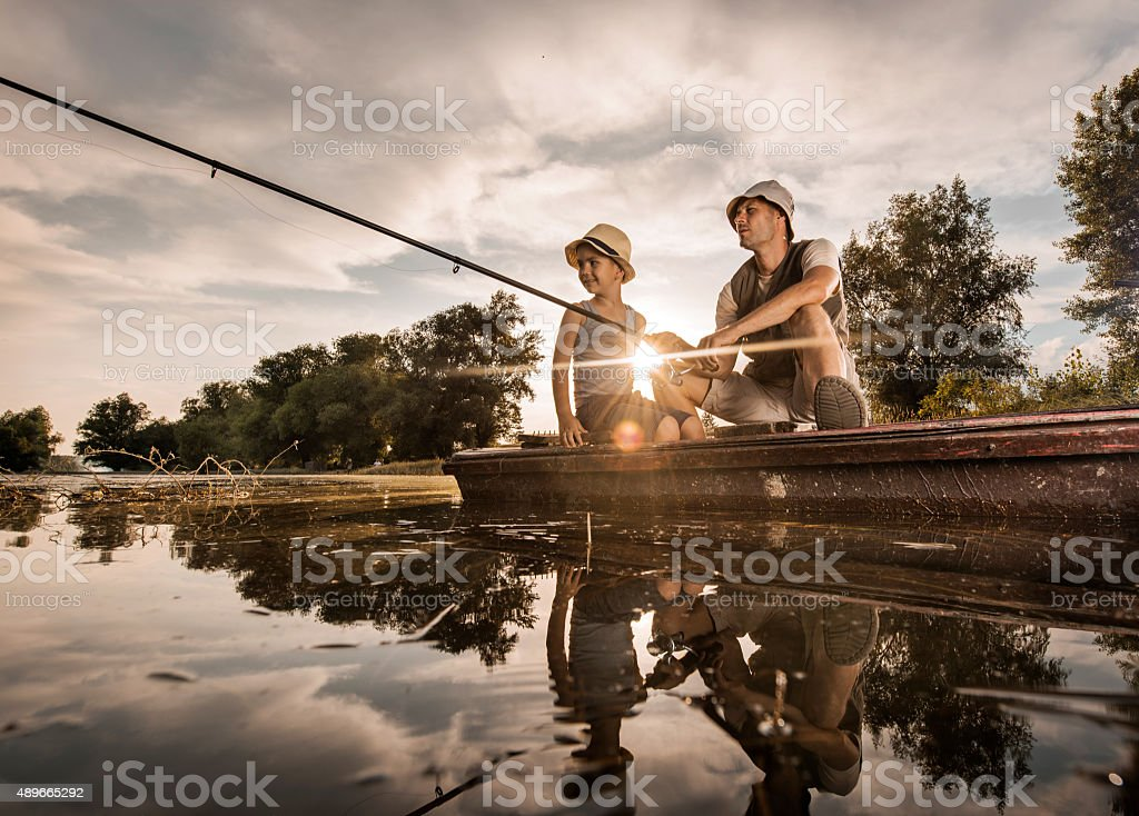 Below view of father and son in fishing at sunset. stock photo