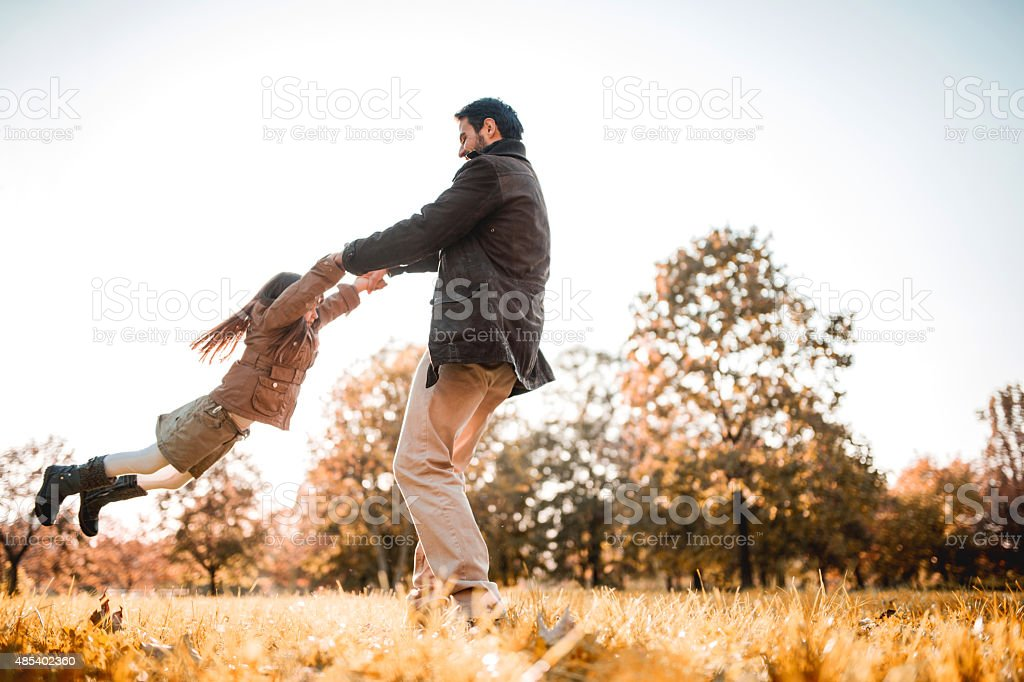 Below view of father spinning his daughter at the park. stock photo