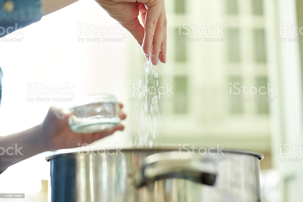 Below view of female hand adding salt to cooking pot stock photo