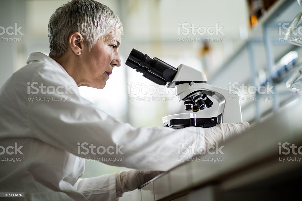 Below view of female scientist looking through a microscope. stock photo
