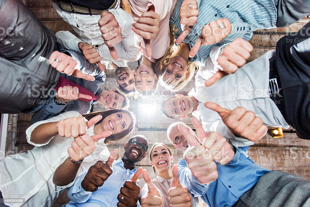 Below view of group of business people showing thumbs up. stock photo