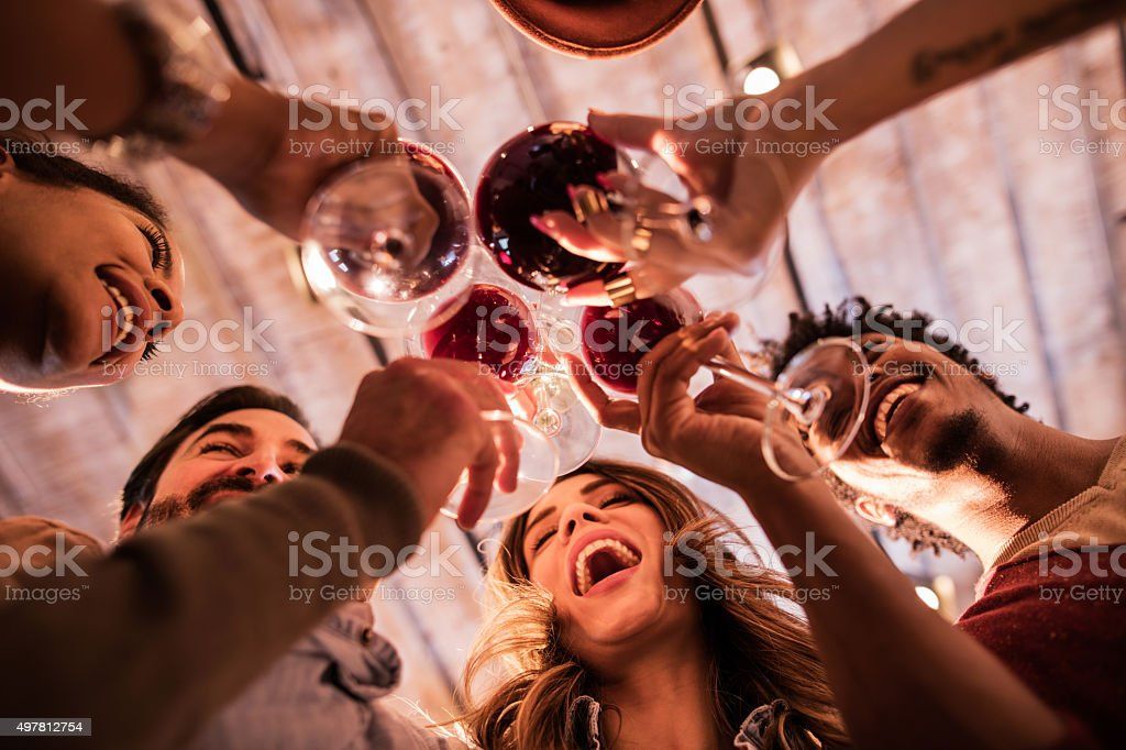 Below view of group of friends toasting with wine. stock photo