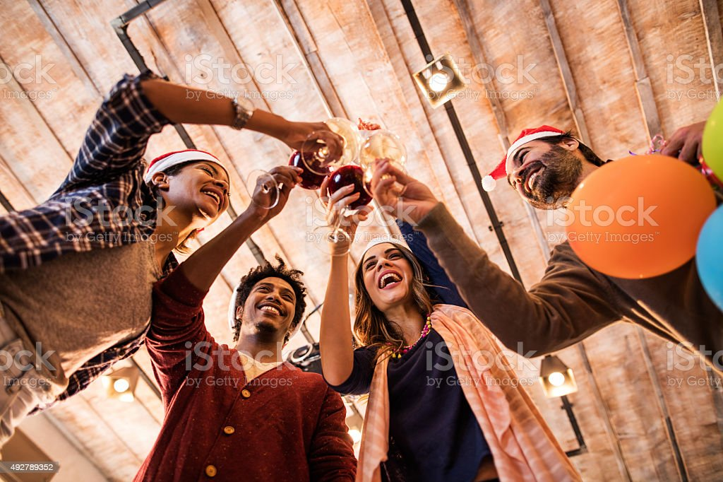 Below view of happy business friends toasting with wine. stock photo