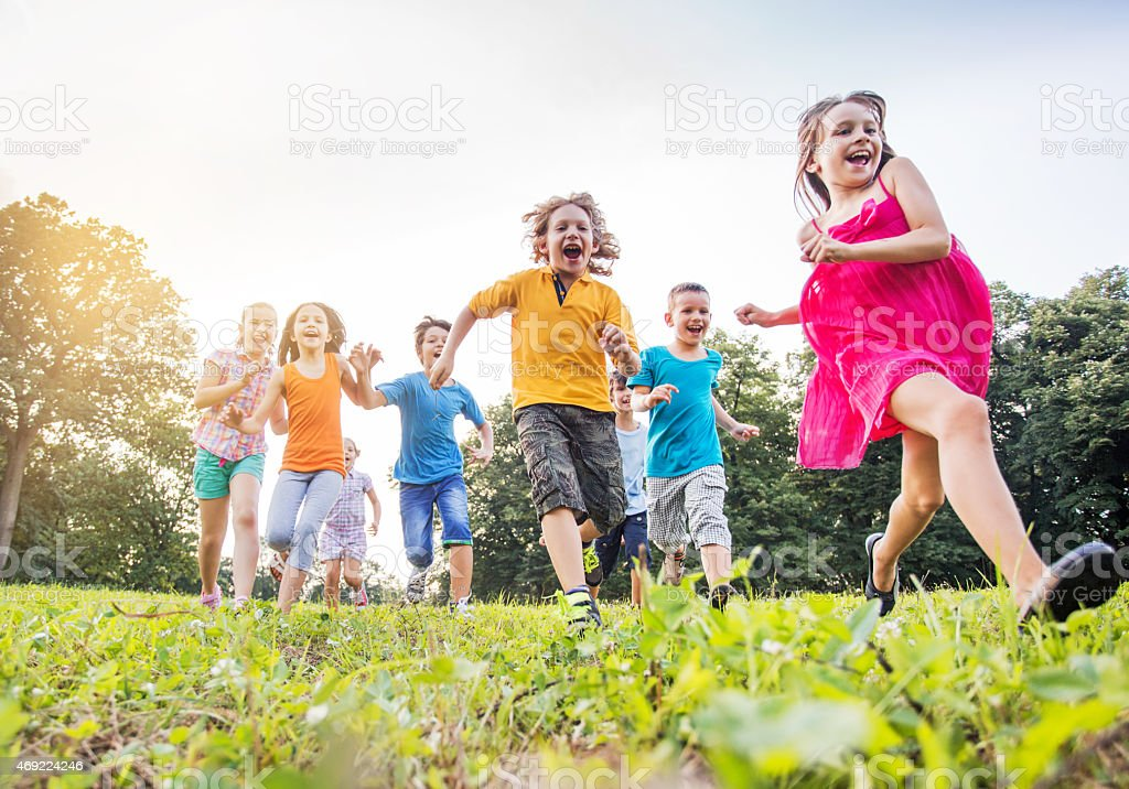 Below view of happy children running in the park. stock photo