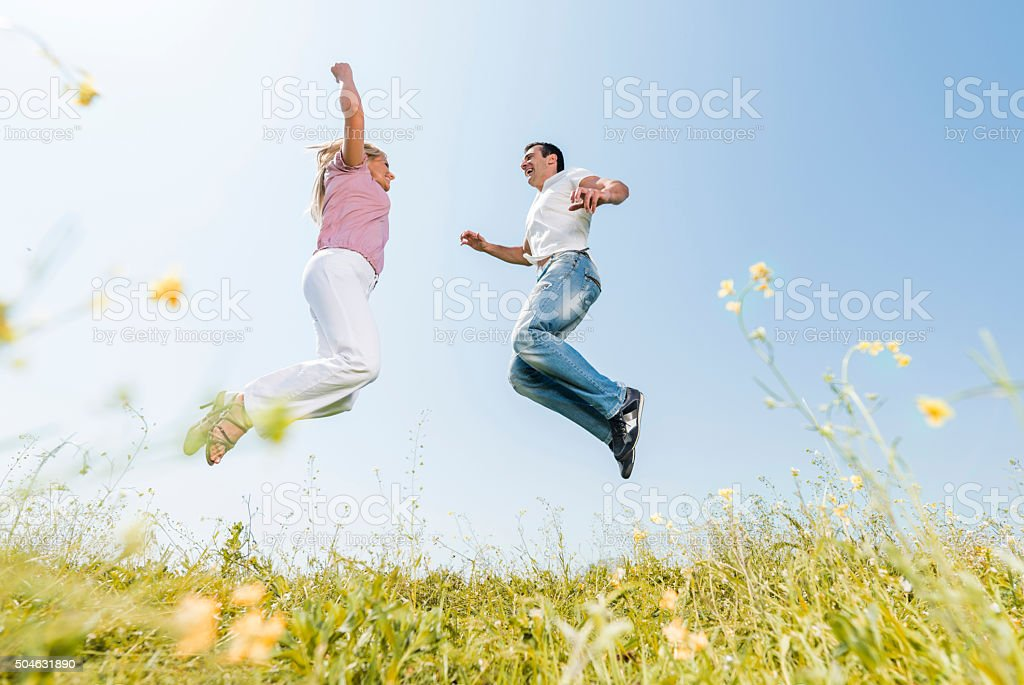 Below view of happy couple jumping in nature. stock photo