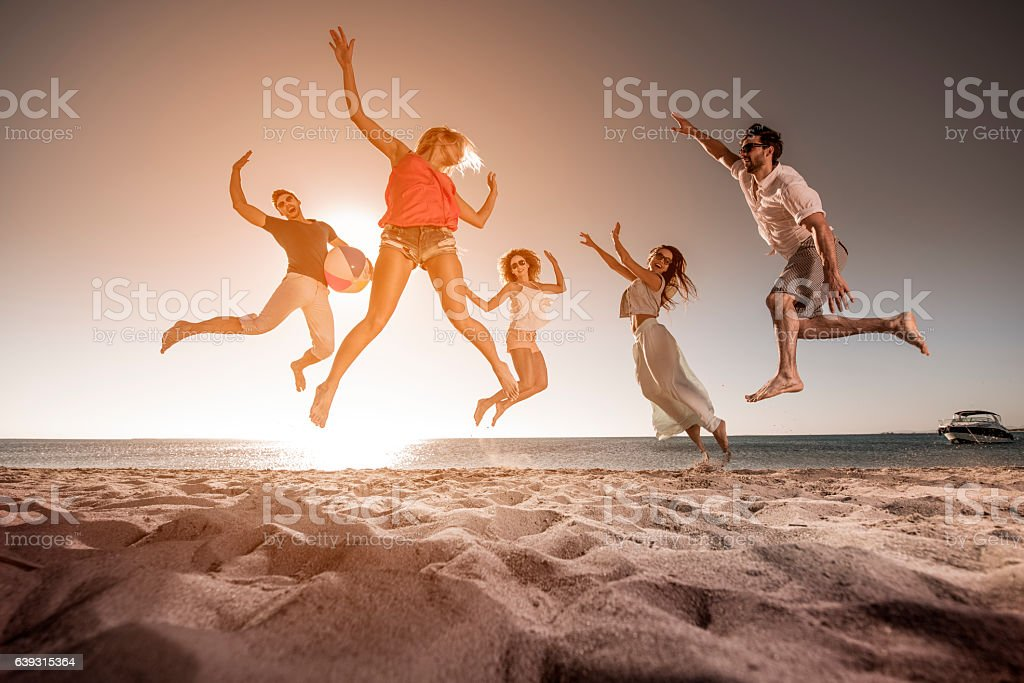 Below view of happy people jumping on the beach. stock photo
