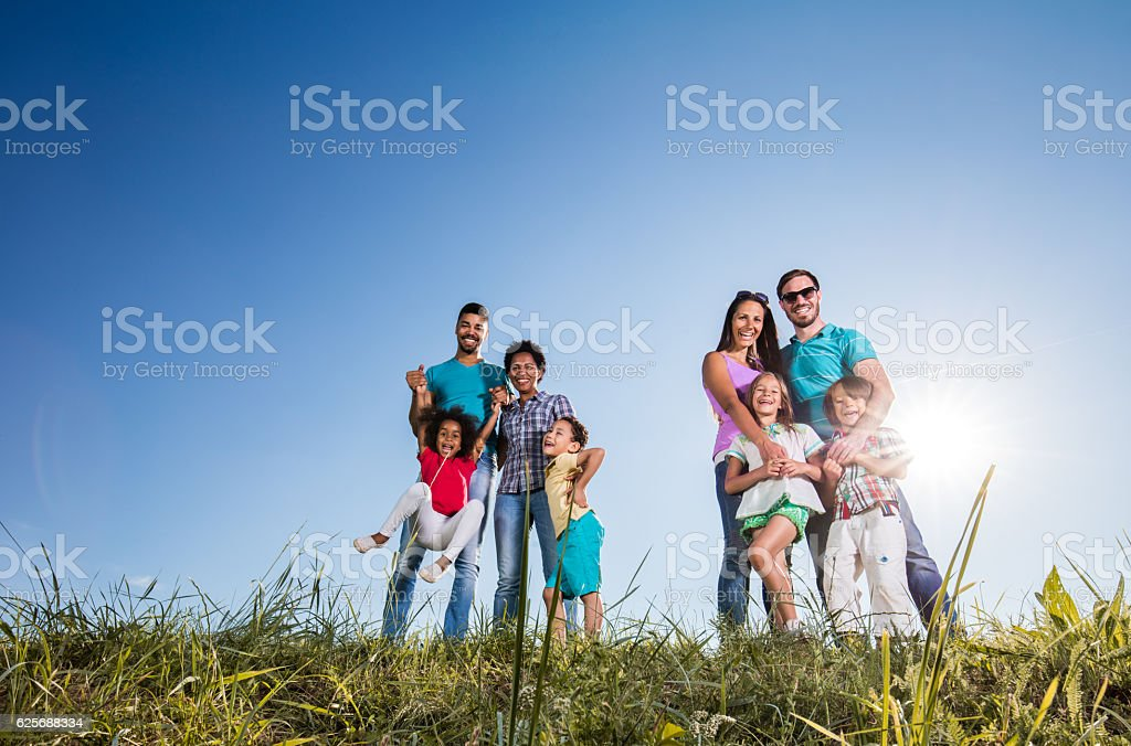 Below view of happy two happy families in a meadow. stock photo