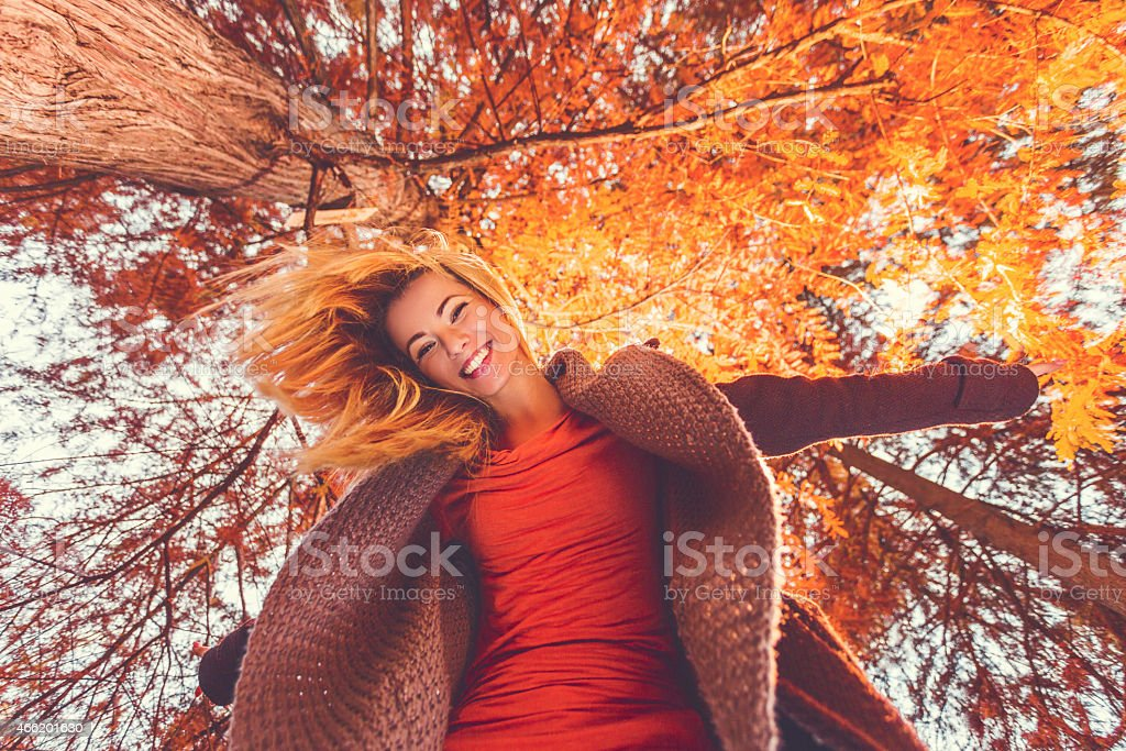 Below view of happy young woman having fun in autumn. stock photo