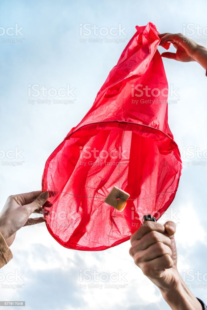 Below view of igniting Chinese lampion with a lighter. stock photo