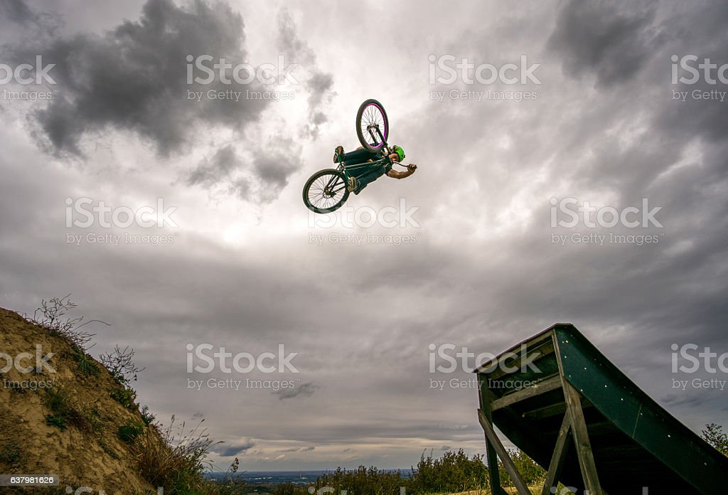 Below view of man doing 360 tabletop on mountain bike. stock photo