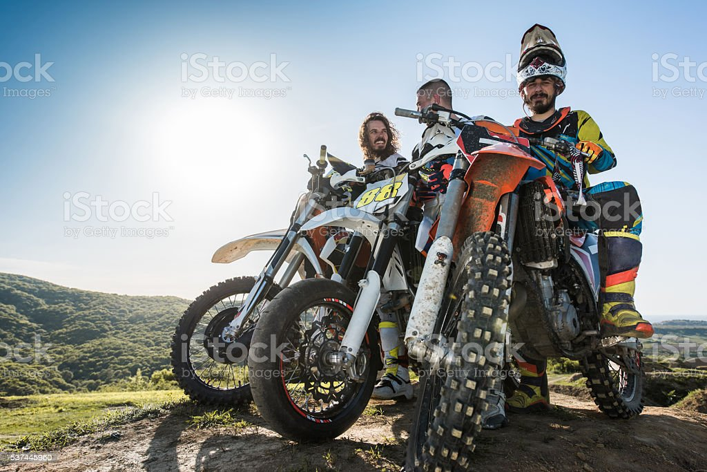 Below view of motocross riders relaxing on bikes in nature. stock photo