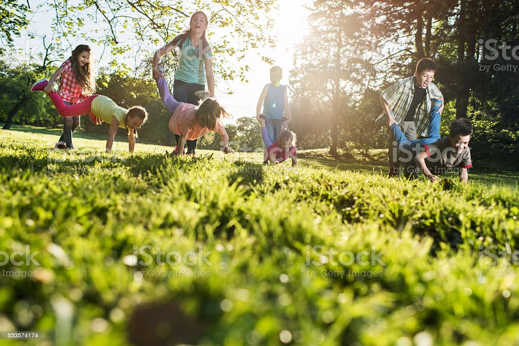 Below view of playful children having fun in wheelbarrow race. stock photo