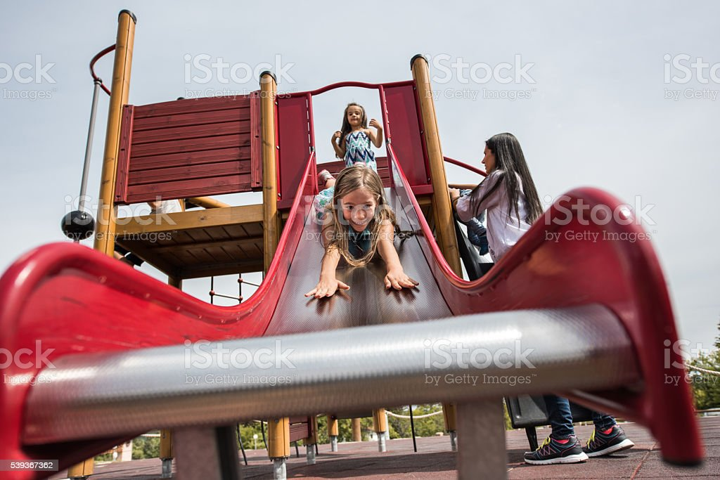 Below view of playful girl having fun on a slide. stock photo