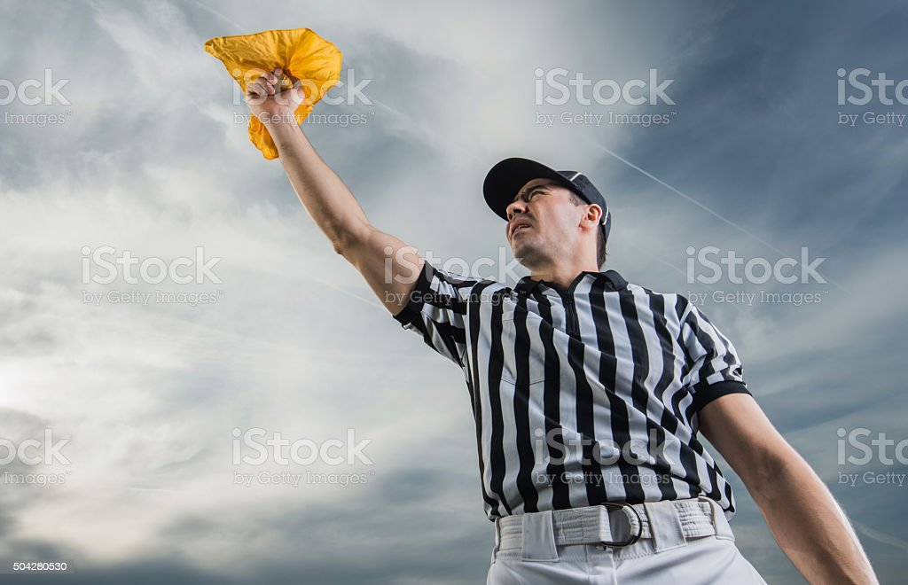 Below view of referee showing penalty against the sky. stock photo