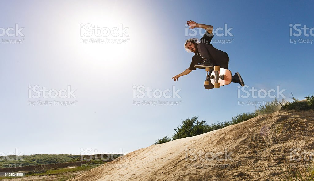 Below view of skilful skateboarder practicing Ollie on dirt road. stock photo