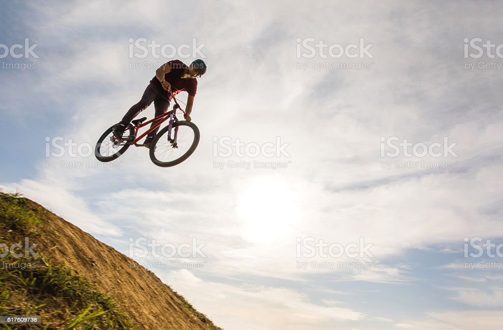 Below view of skillful cyclist jumping high up against sky. stock photo