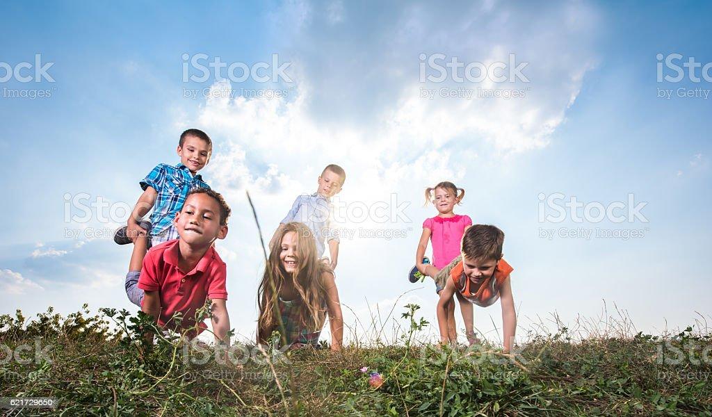 Below view of small kids having a wheelbarrow race outdoors. stock photo