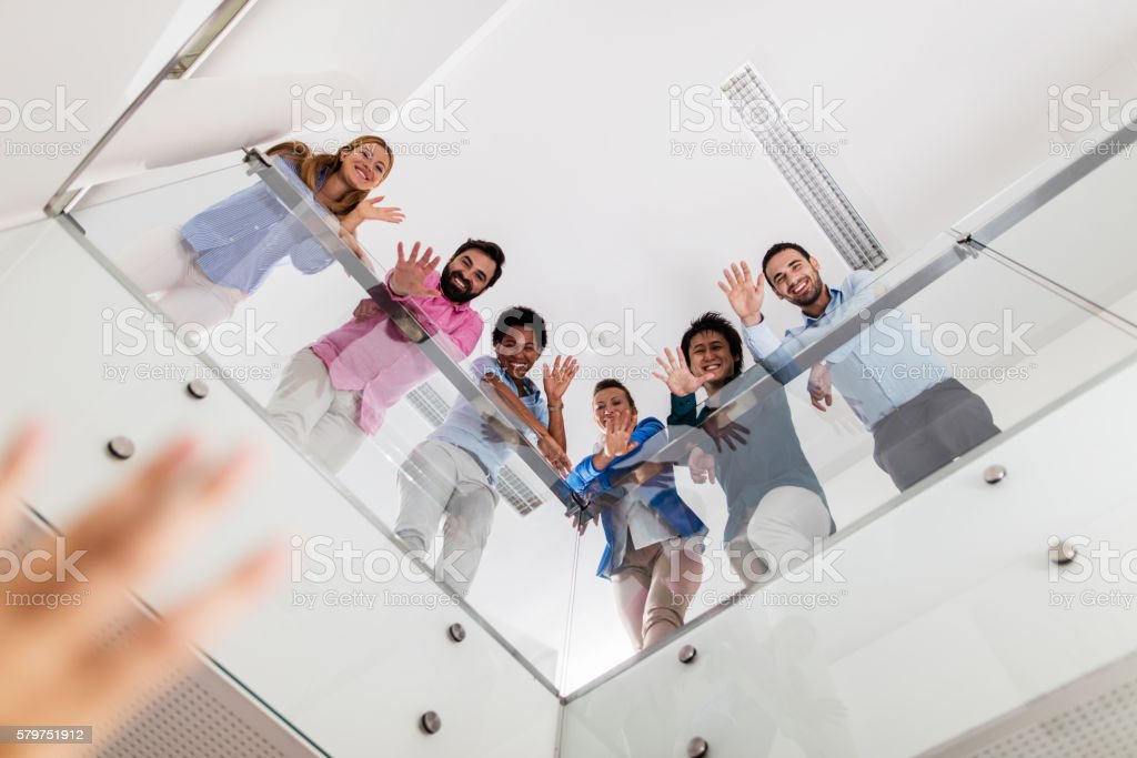 Below view of smiling business people in a hallway waving. stock photo