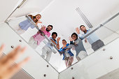 Below view of smiling business people in a hallway waving.