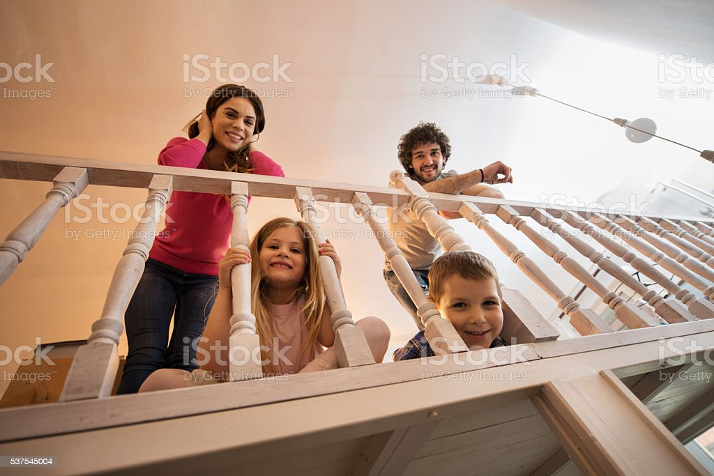 Below view of smiling family leaning on a banister. stock photo