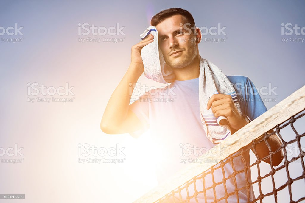 Below view of sportsman wiping sweat against the sky. stock photo