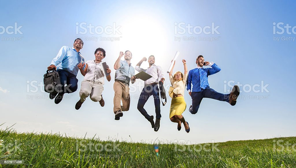 Below view of successful business people jumping in nature. stock photo