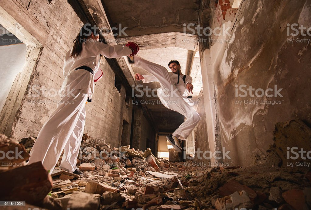 Below view of teakwondo sparring partners exercising among ruins. stock photo