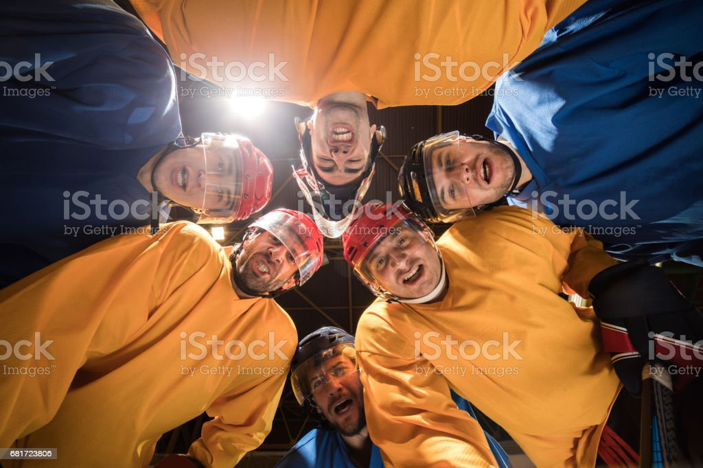Below view of team of ice hockey players making faces and looking at camera. stock photo