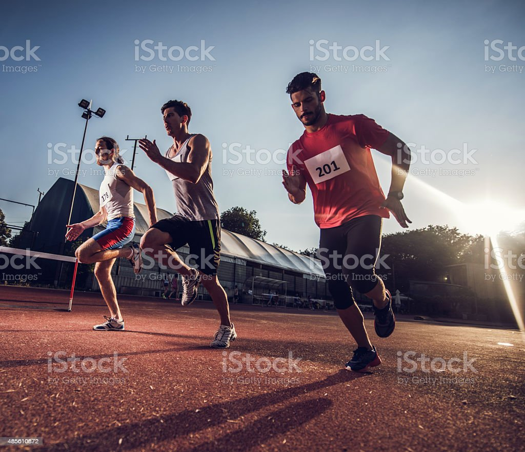 Below view of three male athletes running on sports race. stock photo