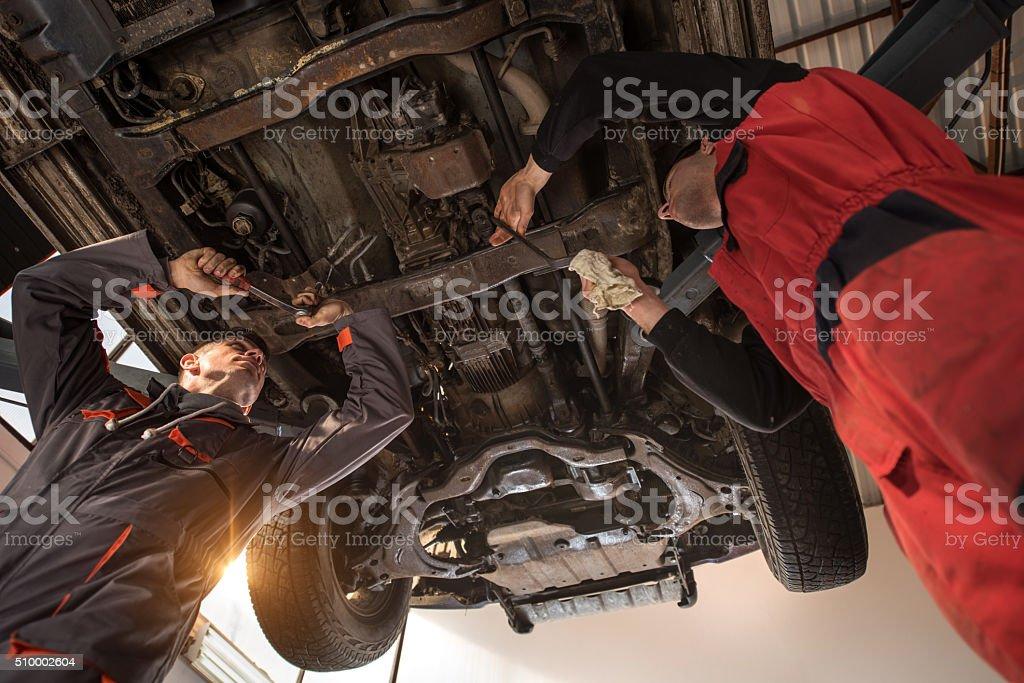 Below view of two mechanics repairing a car. stock photo