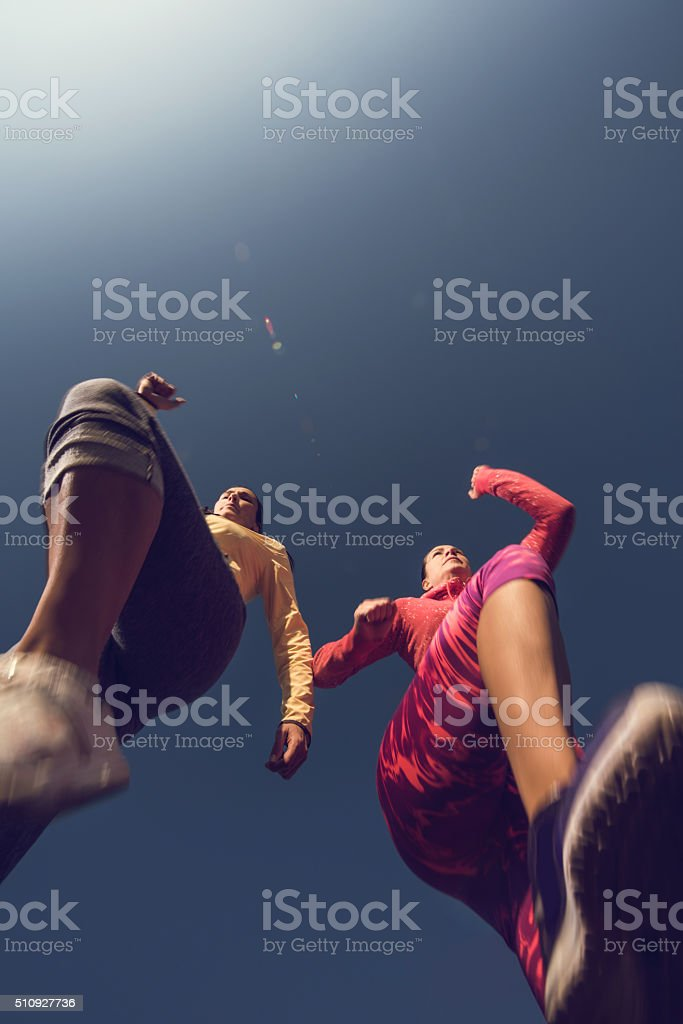 Below view of two women jogging against the sky. stock photo