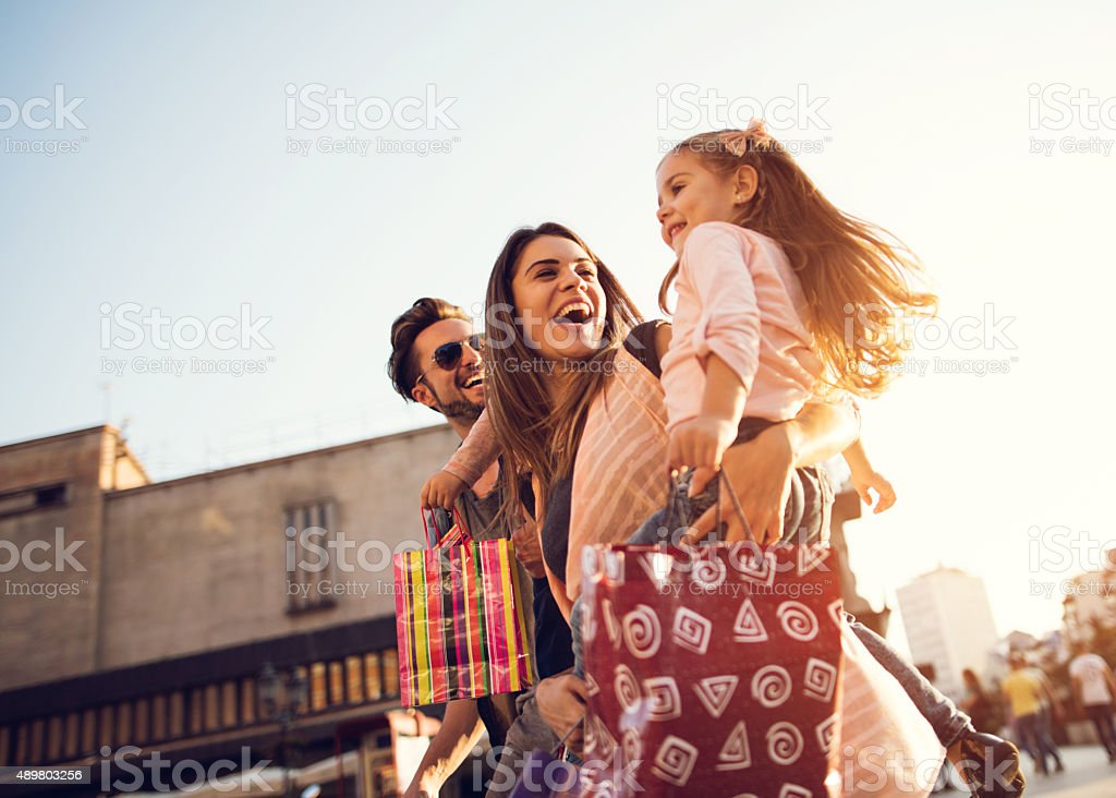 Below view of young cheerful family in shopping. stock photo