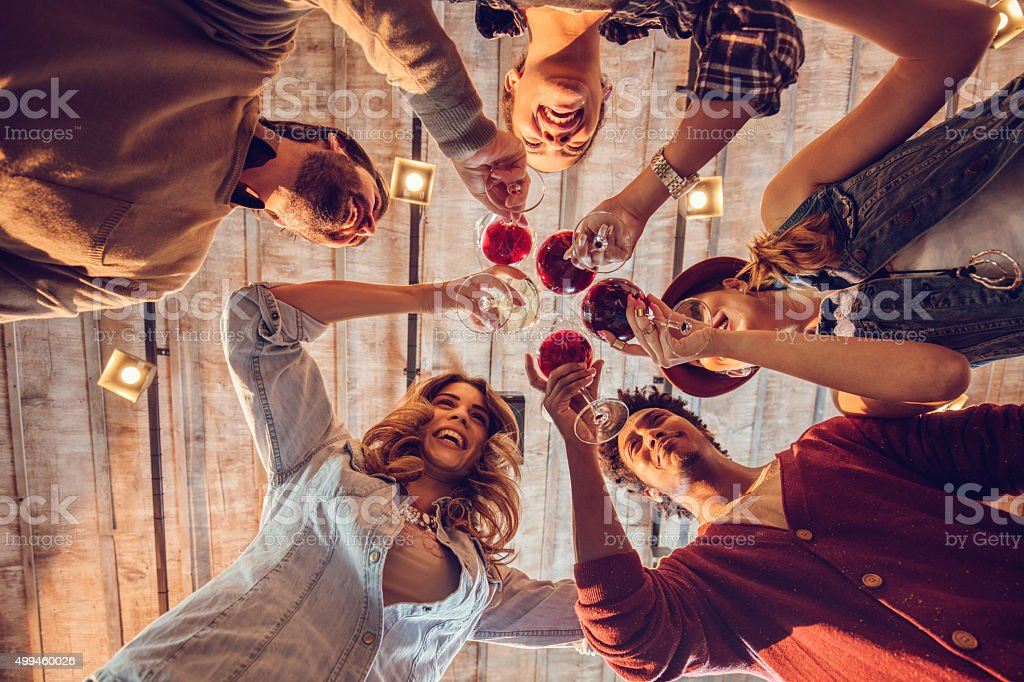 Below view of young happy friends toasting with wine. stock photo
