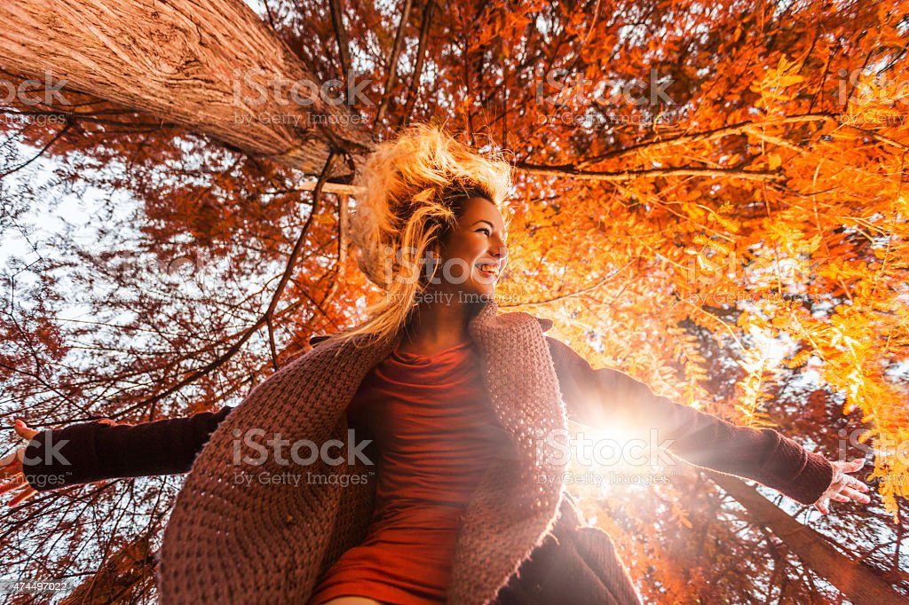 Below view of young happy woman having fun in autumn. stock photo