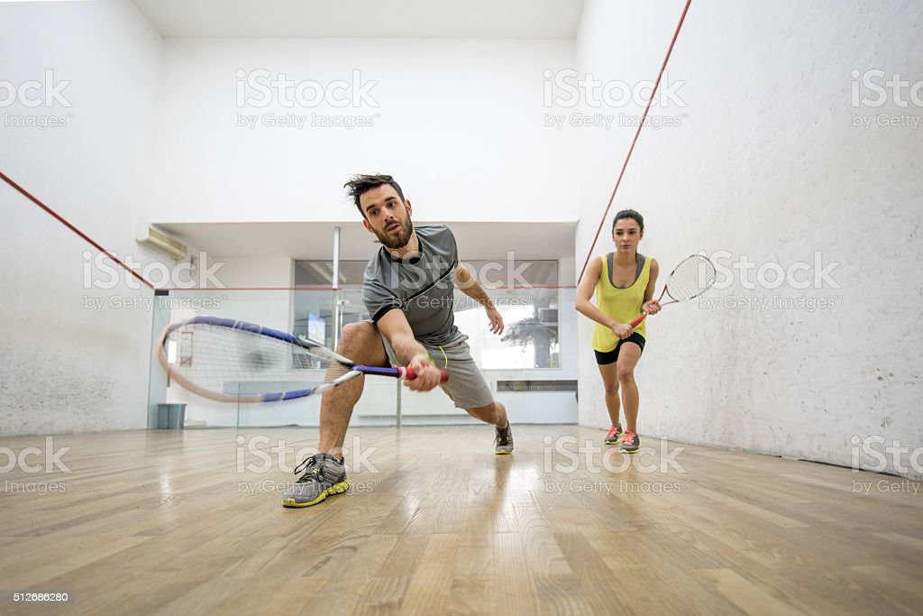 Below view of young man and woman playing squash. stock photo