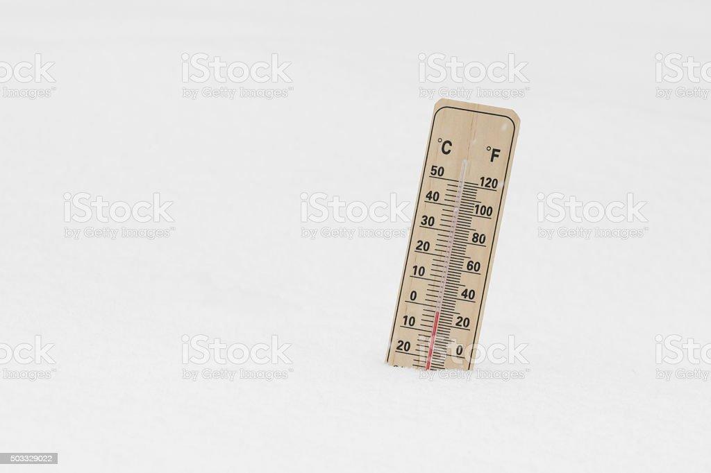 Below Zero degree Celsius temperature on mercury thermometer in snowdrift stock photo