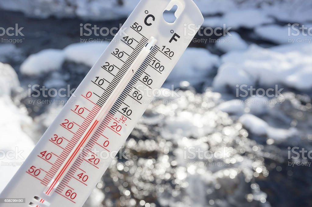 Below Zero degree Celsius temperature with frozen creek in background stock photo