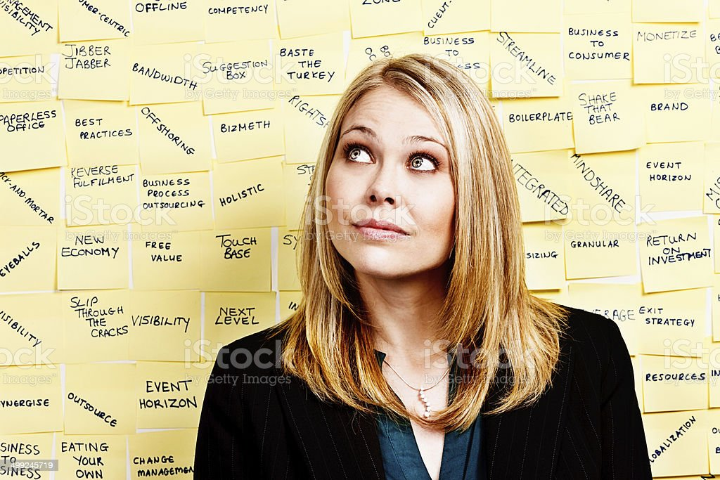Bemused blonde businesswoman doesn't understand wall of business buzzwords stock photo
