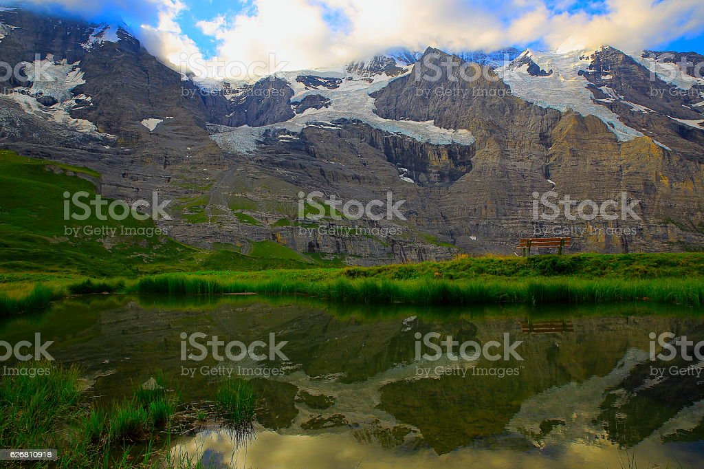 Bench and mirrored lake under Jungfrau and Monch massif: Swiss Alps stock photo
