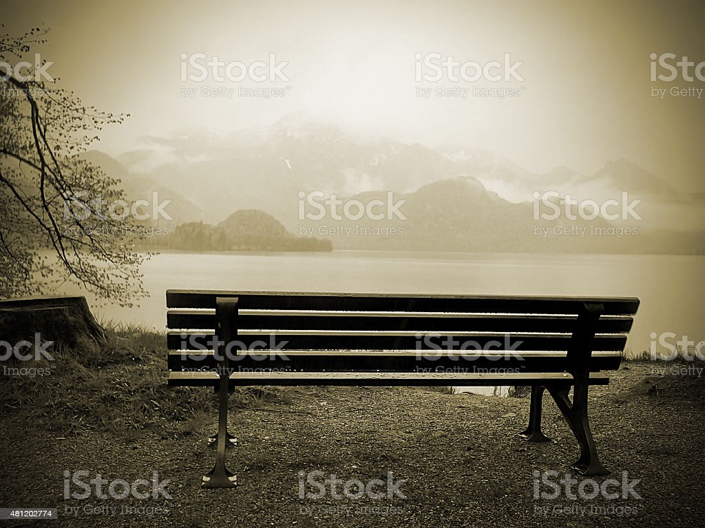 bench at a lake with mountains in background stock photo