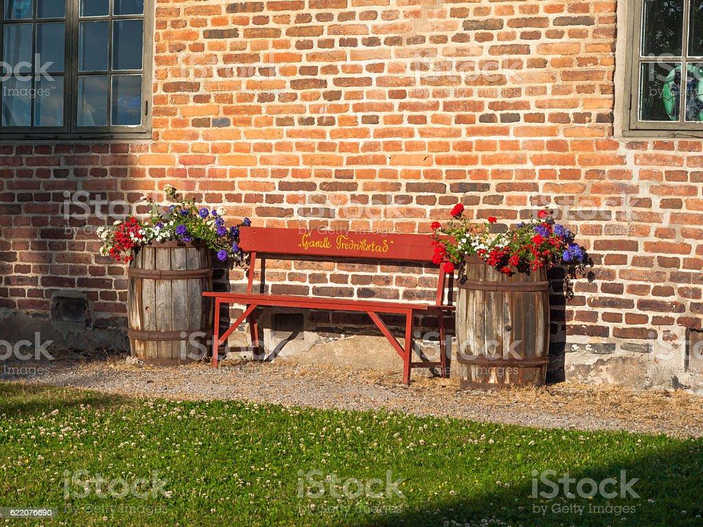 Bench between flowers in barrels stock photo