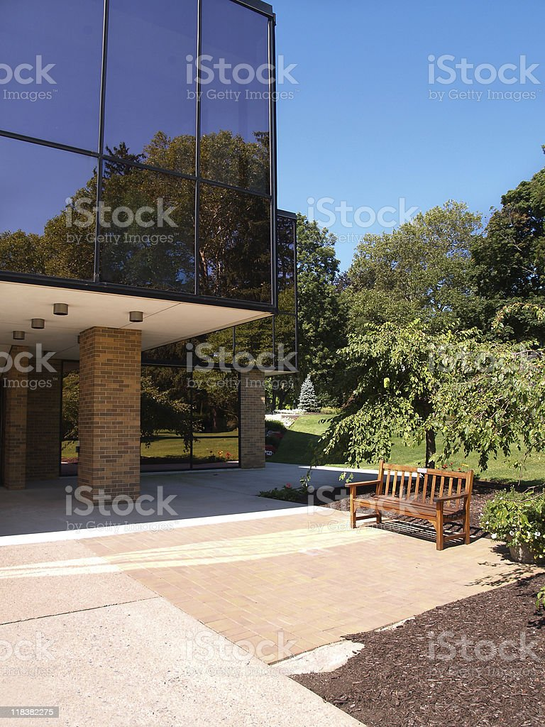 bench by glass building stock photo