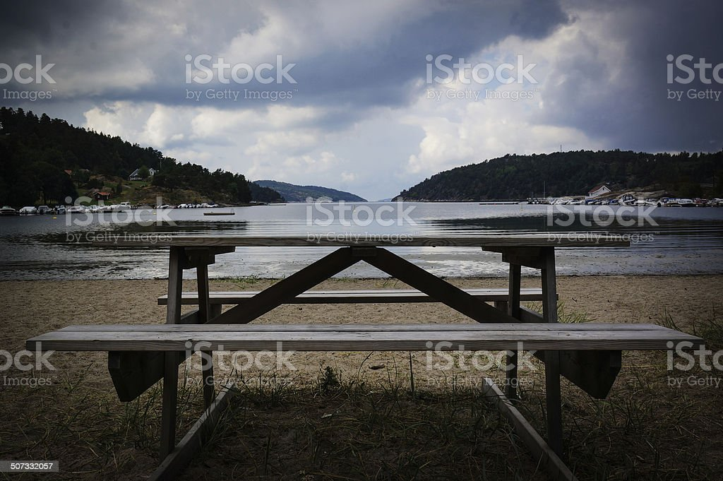 Bench by small beach and fjord royalty-free stock photo
