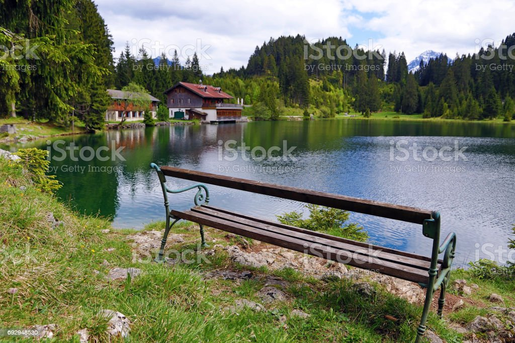 A bench in front of a lake in the mountains in Austria stock photo