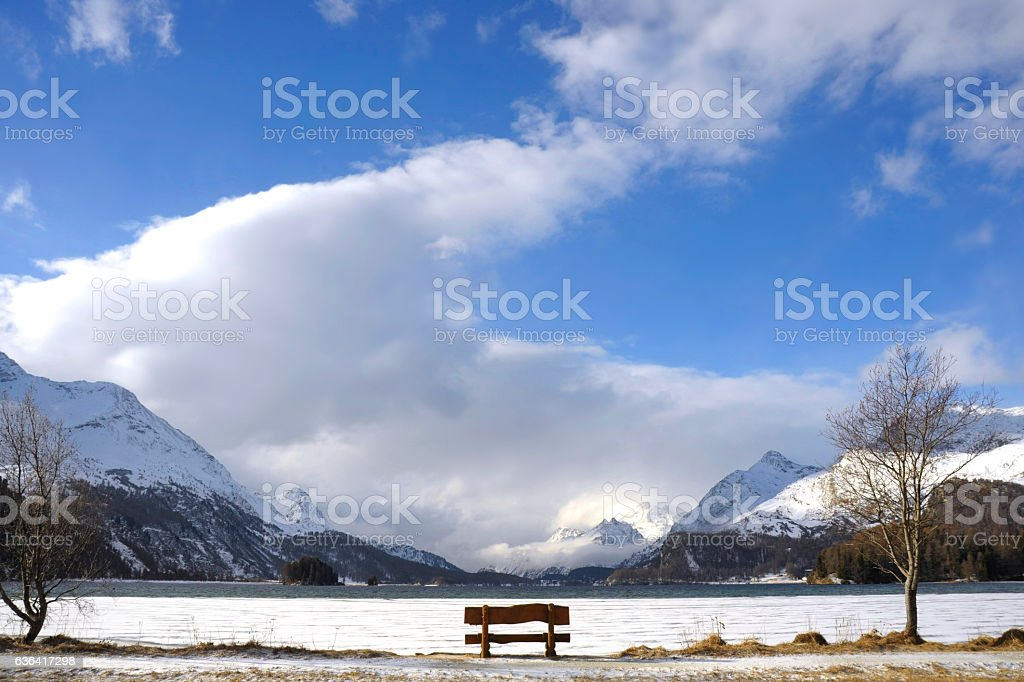 bench looking solitary at Sils lake in Switzerland Alps mountains stock photo