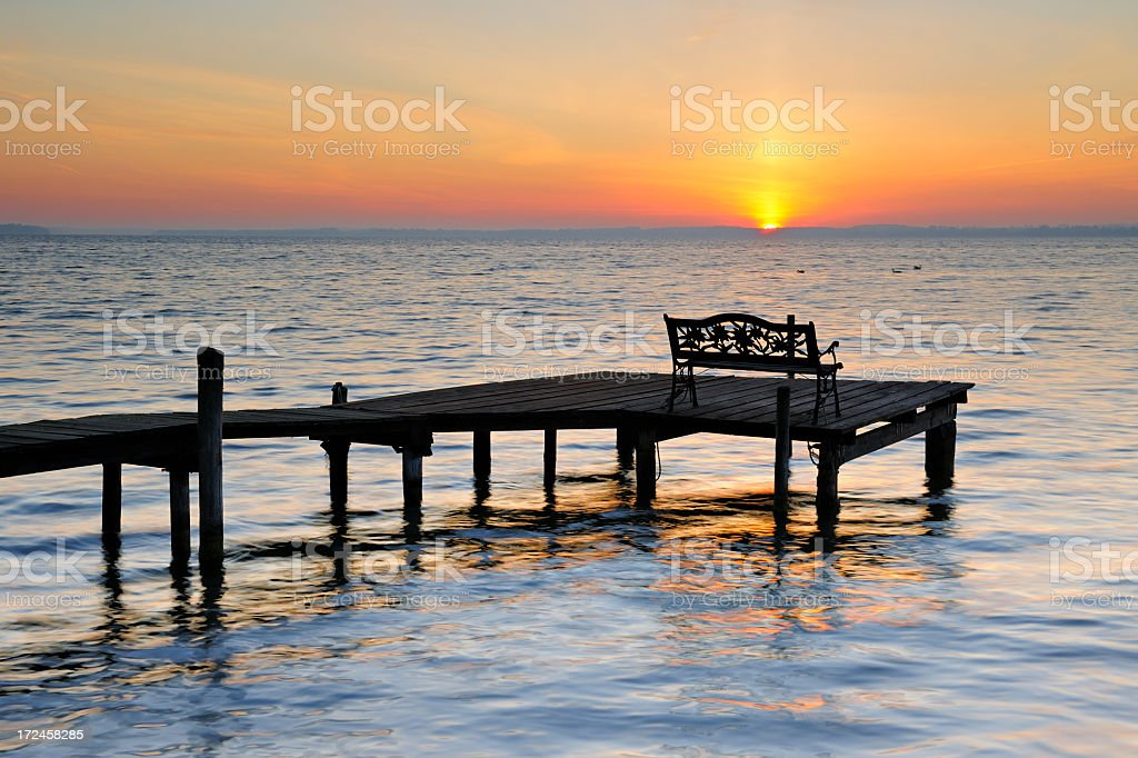 Bench on Dock by Lake at Sunrise royalty-free stock photo