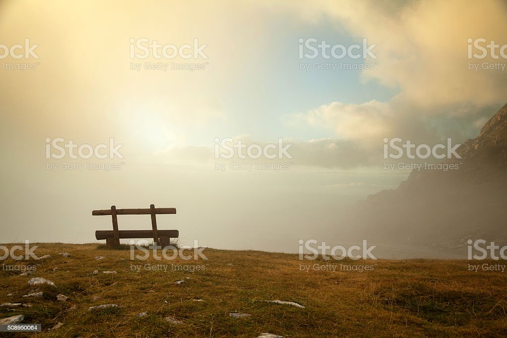 Bench on edge of the hill in the misty morning stock photo