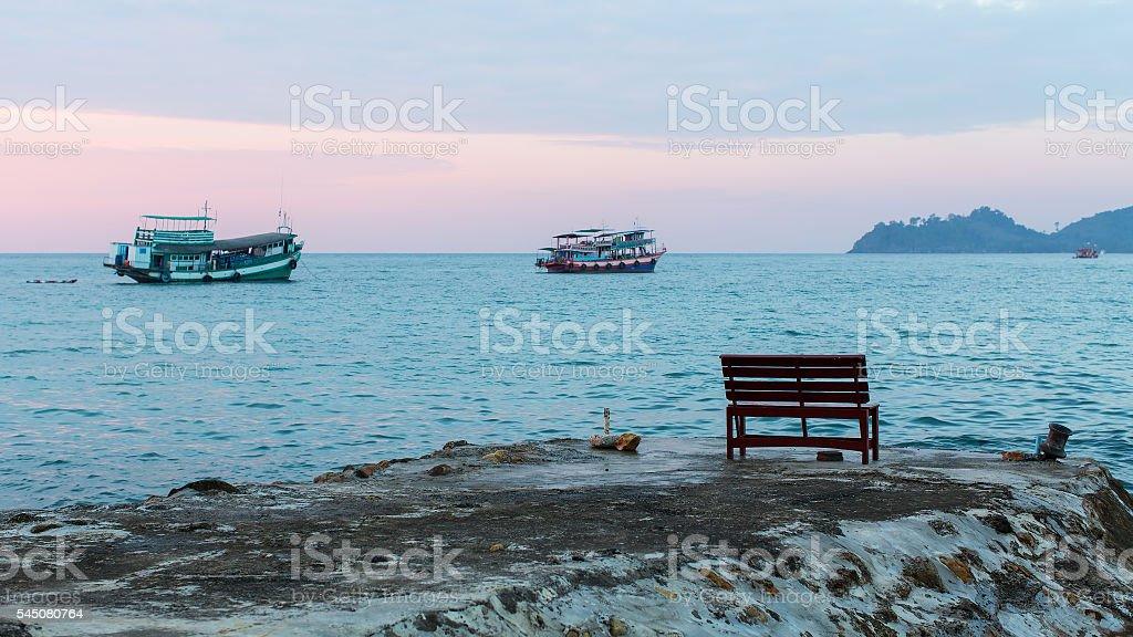 Bench on the seaside promenade at dusk. stock photo