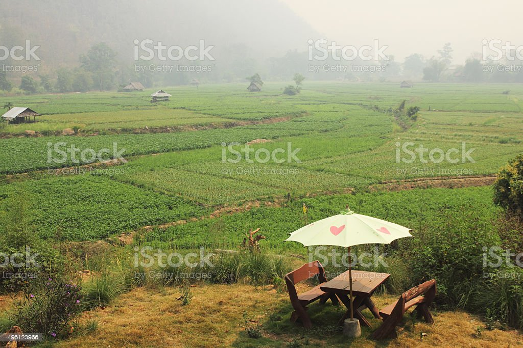 Bench outdoor with umbrella beside nice view mountain. stock photo