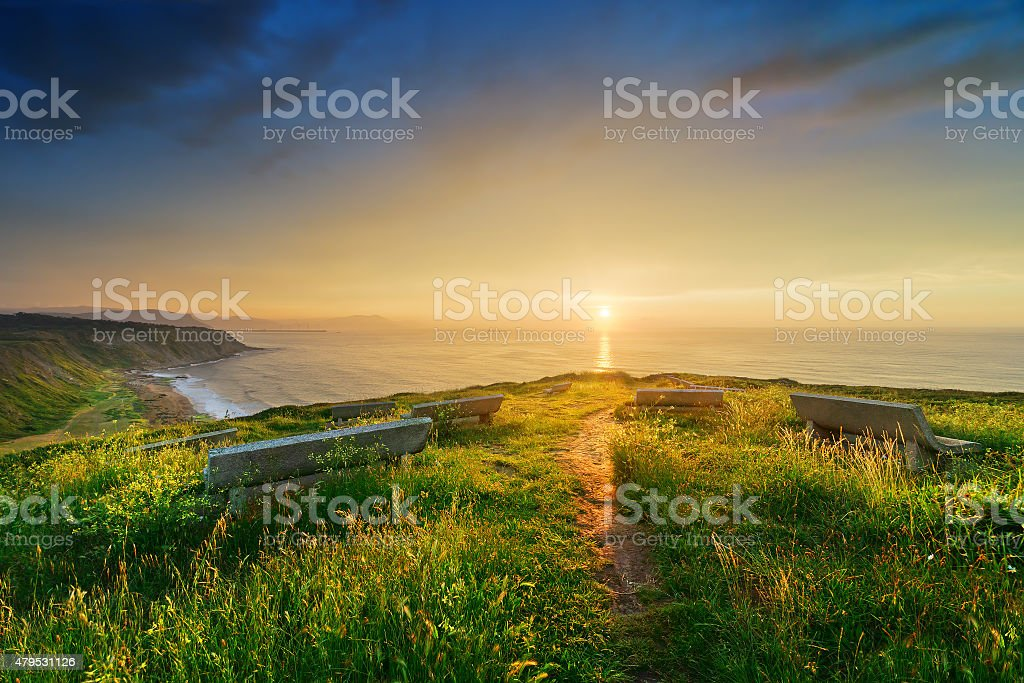 Benches near Azkorri beach with stormy weather at sunset stock photo